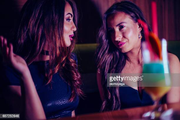 Two stunning girls having cocktails
