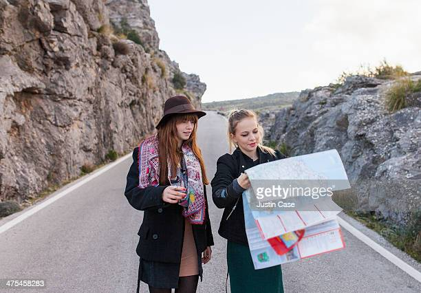 two stylish girls looking at a map on the road