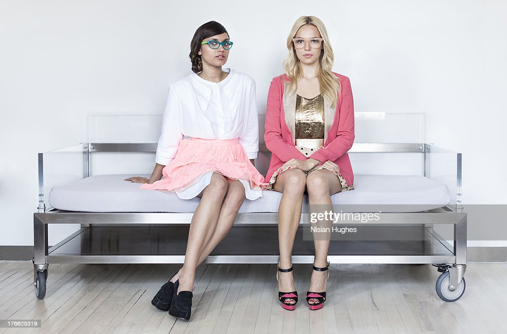 two stylish young women sitting on a modern couch : Stock Photo