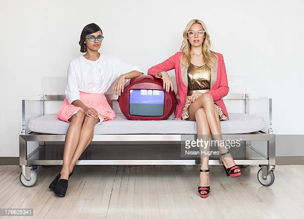 two stylish young women sitting on couch with TV