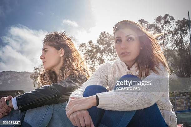 Two sullen young women friends sitting on breezy beach