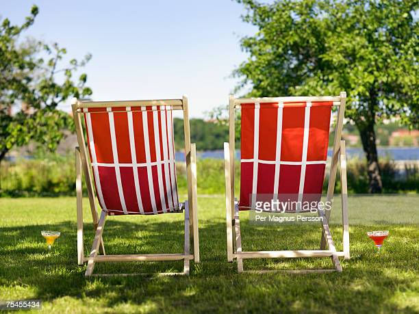 Two sun chairs in a garden.