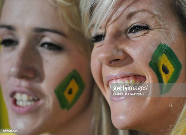 Two supporters of Brazil with the national colours painted on their cheeks smile in the stands before the Fifa Confederations Cup football match...