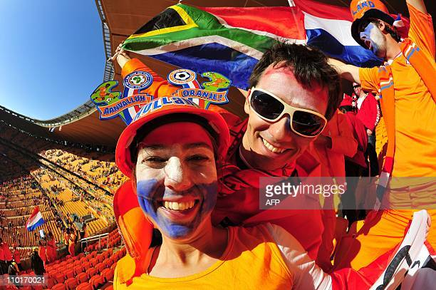 Two supporters of the Netherlands one with a makarapa supporting the Dutch team another with a South African flag cheer in the stands of Soccer City...
