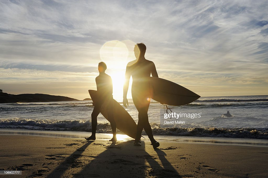Two surfers coming out of the water at sunset : Stock Photo