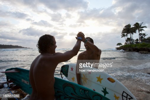 Two surfers high five on the beach : Stock Photo