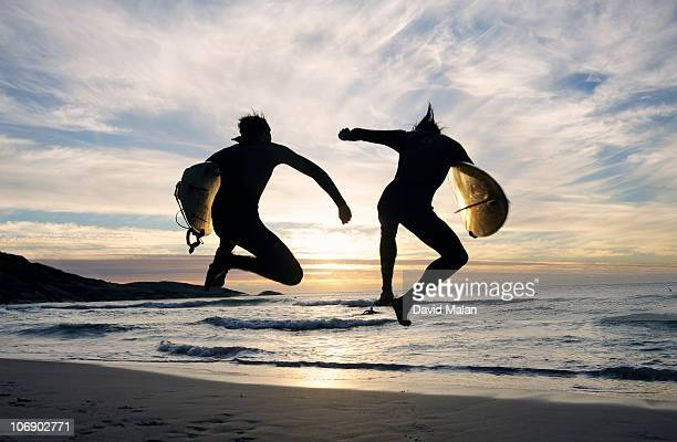 Two surfers leaping with joy.