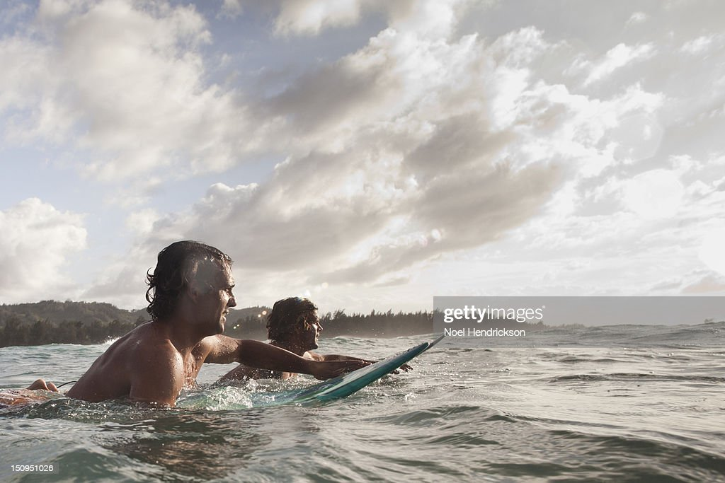 Two surfers paddle out to catch waves : Stock Photo