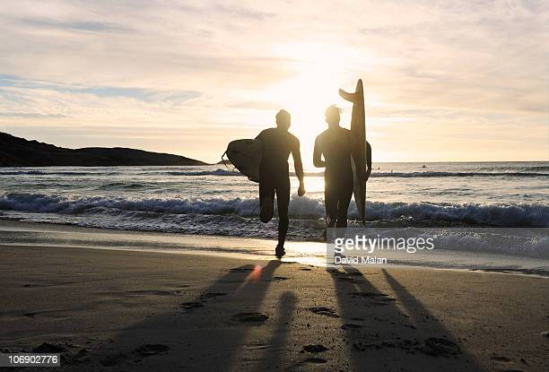Two surfers running into the sea at sunset