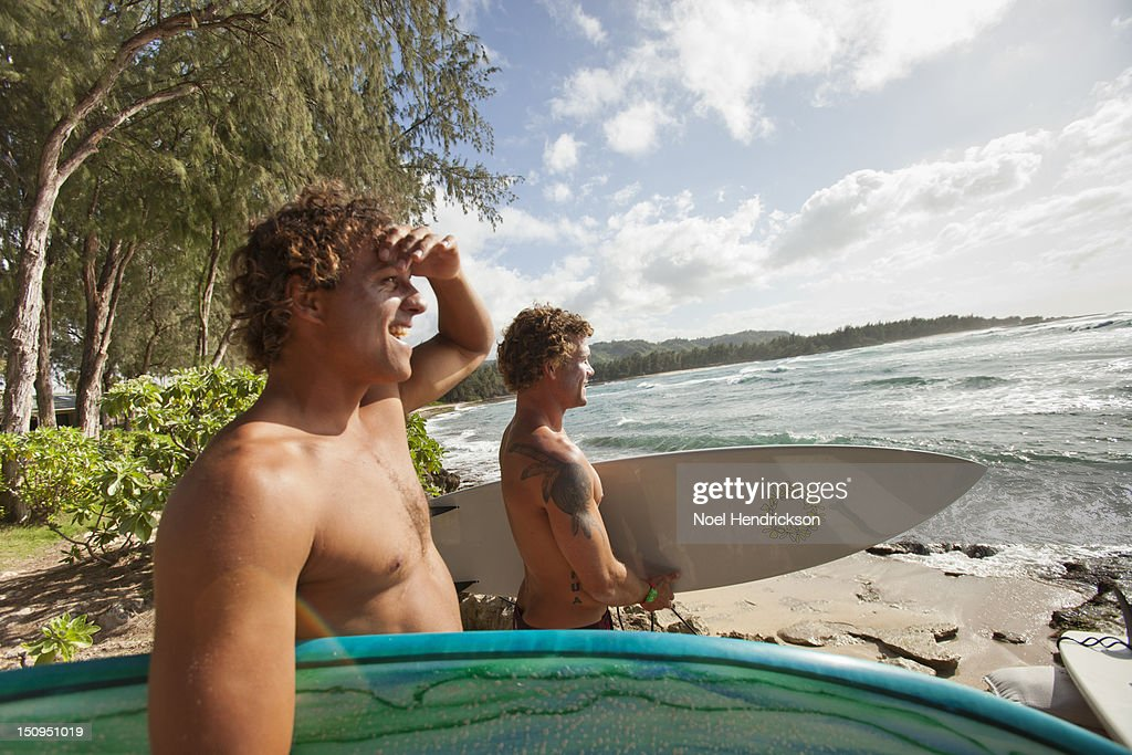 Two surfers survey the ocean from the beach : Stock Photo