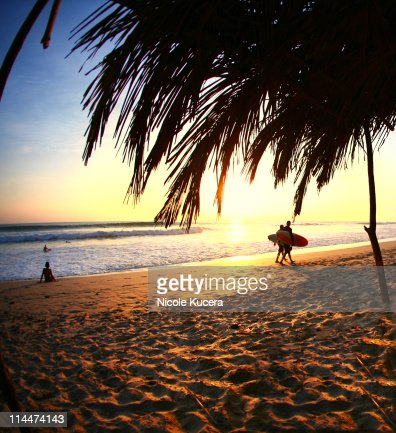 Two surfers walking at sunset in Costa Rica