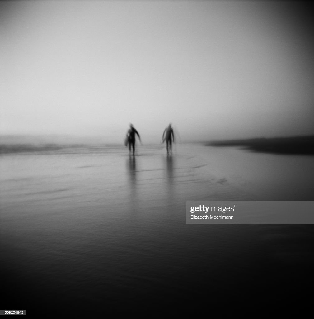 Two surfers walking up the beach, black and white