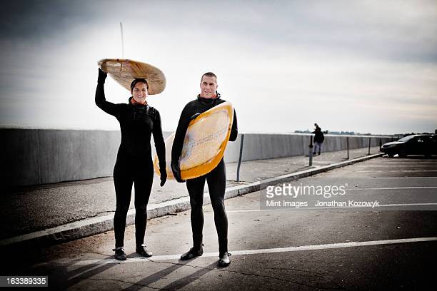 Two surfers wearing wetsuits carrying their boards.