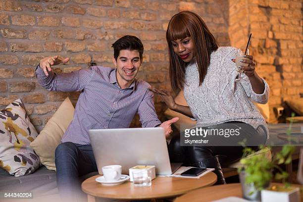Two surprised coworkers watching something on laptop in a cafe.