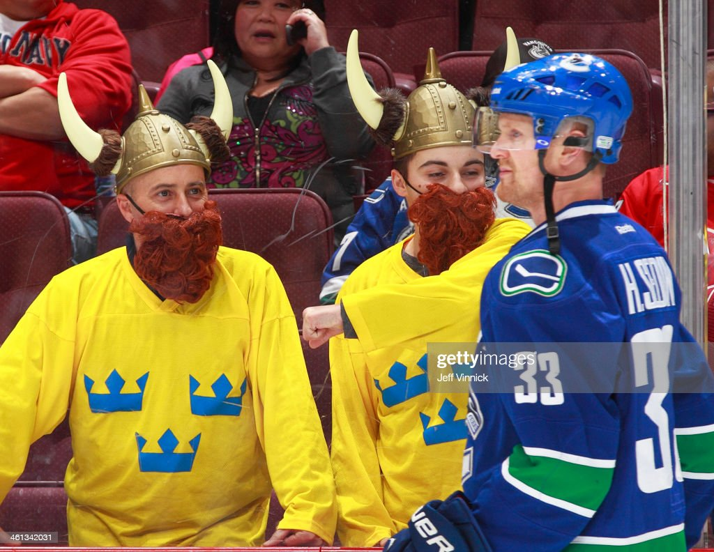 Two Swedish fans watch <a gi-track='captionPersonalityLinkClicked' href=/galleries/search?phrase=Henrik+Sedin&family=editorial&specificpeople=202574 ng-click='$event.stopPropagation()'>Henrik Sedin</a> #33 of the Vancouver Canucks during the warmup before their NHL game against the Pittsburgh Penguins at Rogers Arena January 7, 2014 in Vancouver, British Columbia, Canada. Pittsburgh won 5-4.
