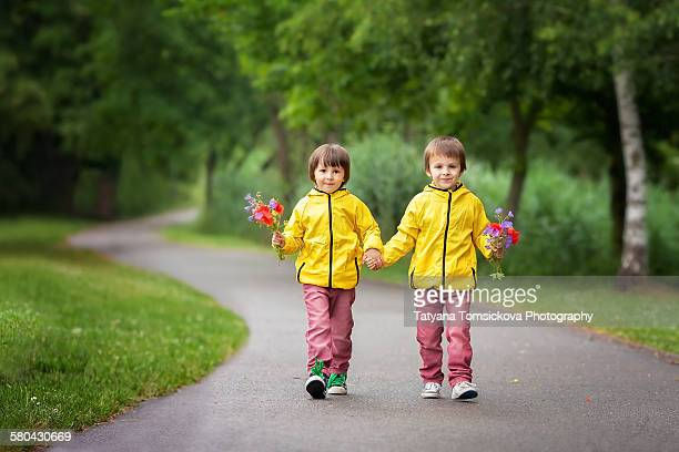 Two sweet boys in park, holding flowers