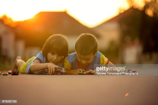 Two sweet children, boy brothers, playing with car toys on the street in village on sunset, summertime