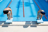 Two swimmers on starting blocks