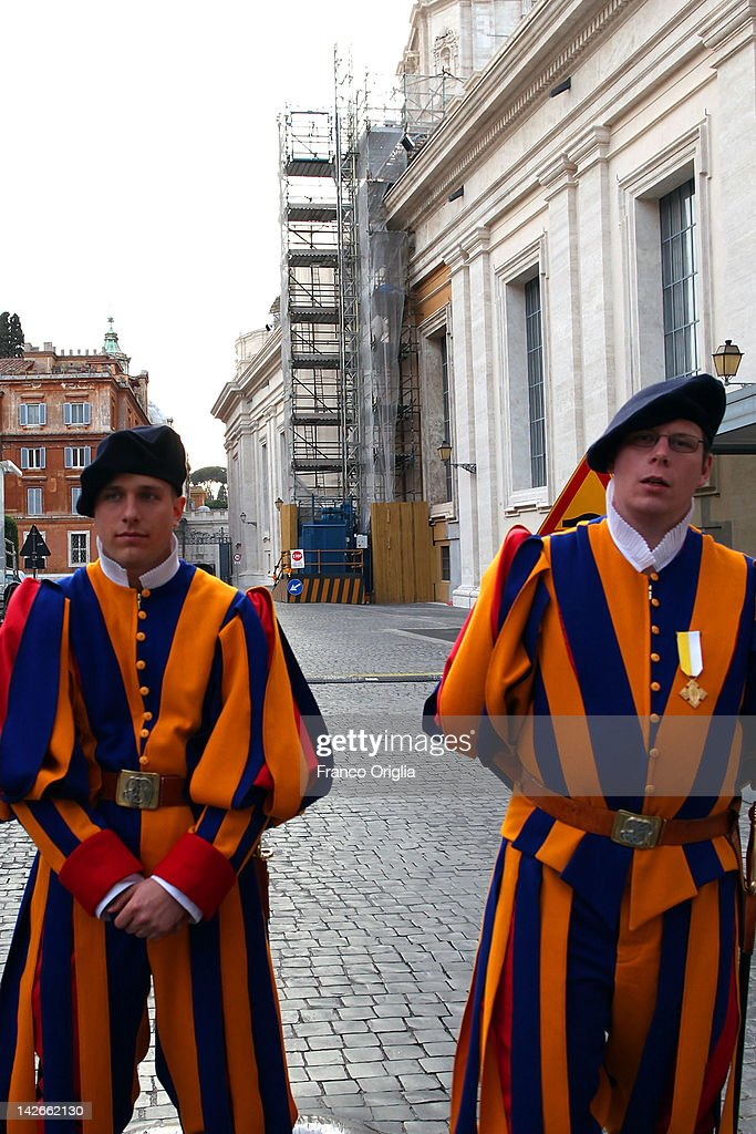 Two Swiss Guards stand in front of an elevator installed for the restoration works of the colonnade of Gian Lorenzo Bernini, in St. Peter's Square on April 10, 2012 in Vatican City, Vatican. The square was designed by architect Gian Lorenzo Bernini in 1656. The two semi-circles of the colonnade are surrounded by 140 statues and 244 columns. Guy Devreux of the Vatican Laboratory for Marble and Cast began direction of the works in 2009.