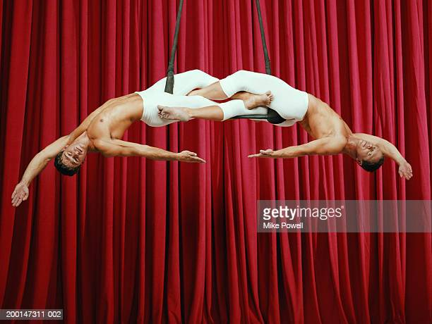 Two synchronized male aerialist performing on trapeze, portrait