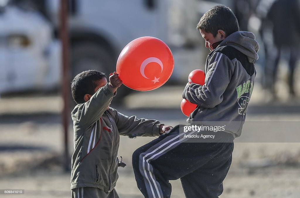 Two Syrian kid who flee the attacks of Syrian and Russian air forces, play with baloons as they shelter at tents and try to live their lives with humanitarian aid send by Turkey, UNHCR and other Turkish Humanitarian aid organizations, close to the Bab al-Salameh border crossing on Turkish-Syrian border near Azaz town of Aleppo, Syria on February 10, 2016.