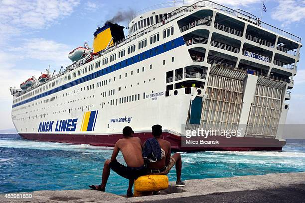 Two Syrian refugees sit at the dock of the port of Kos as the passenger ship 'Eleftherios Venizelos' backs into the quay on the Greek island of Kos...