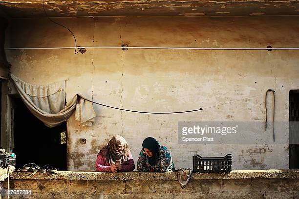 Two Syrian woman talk inside of a former prison now being occupied by Syrian refugees in the Bekaa Valley close to the border with Syria on November...