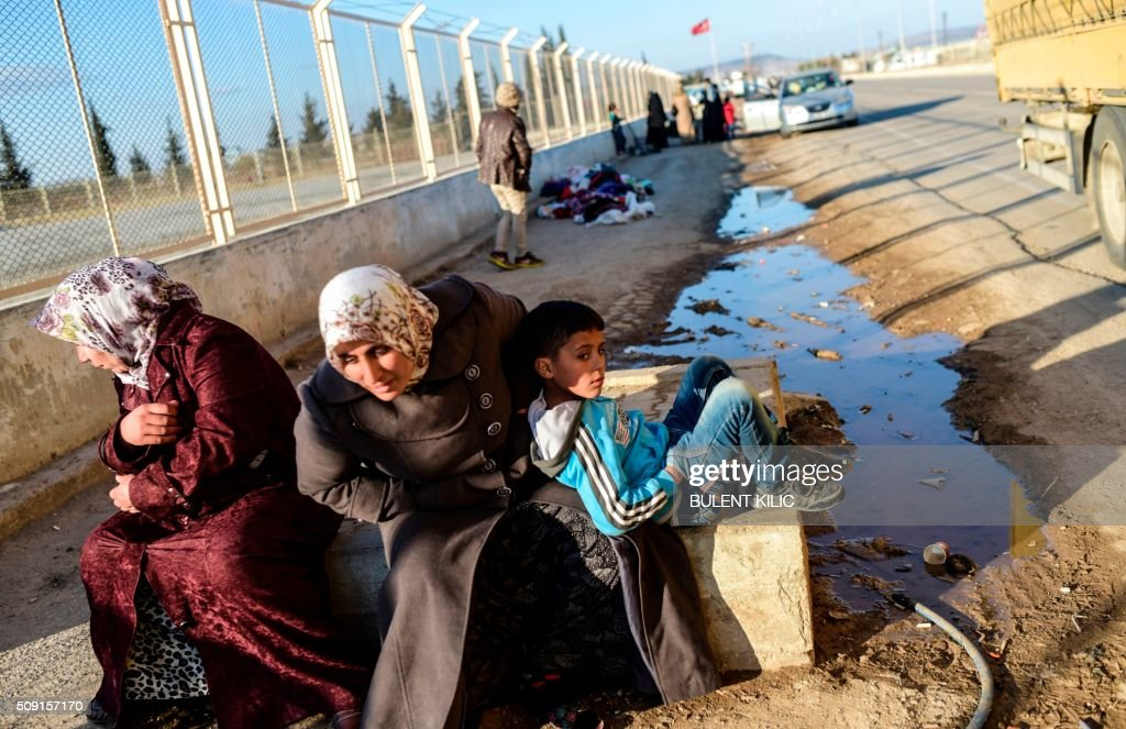 Two Syrian women and a boy wait in front of Oncupinar crossing gate, near the town of Kilis, to return to Syra on February 9, 2016. Around 30,000 Syrians are at the Turkish border after fleeing a Russia-backed regime offensive on the northern region of Aleppo, Turkish Prime Minister Ahmet Davutoglu said on February 8, as his country faces mounting pressure to open its border. Davutoglu said the refugees would be admitted if need be, although Turkey should not be expected 'to shoulder the refugee issue alone.'. / AFP / BULENT KILIC