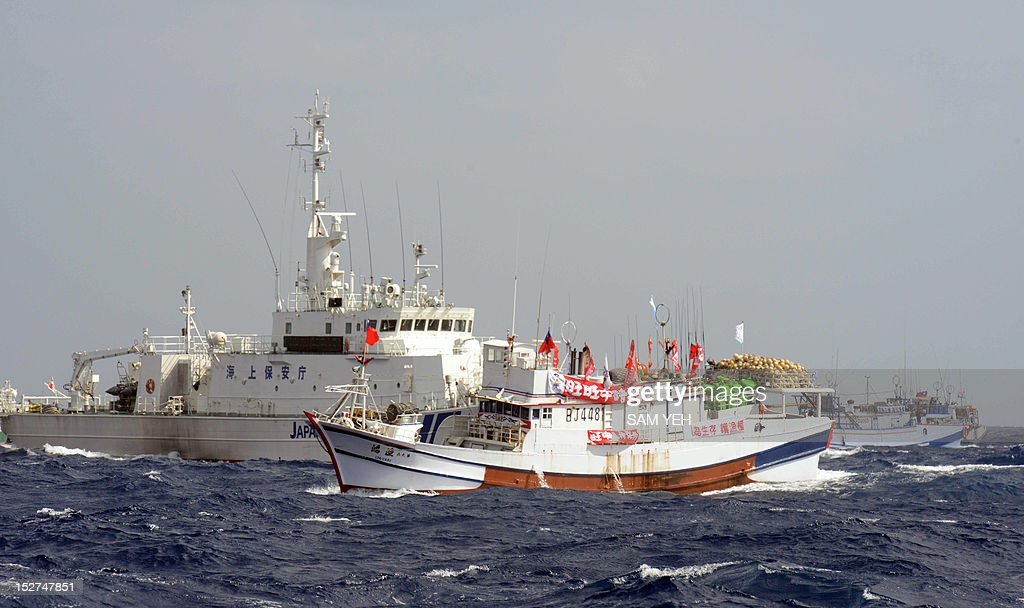 Two Taiwan fishing boats are blocked by a Japan Coast Guard vessel as they try to sail toward the disputed Diaoyu / Senkaku islands in territorial...