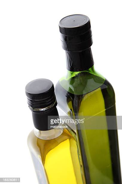 Two tall bottles, a green tinted and a clear, of olive oil.