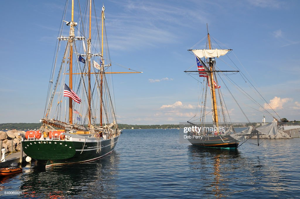 Two tall ships passing in harbor