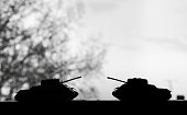 two tanks opposite the silhouette in the dark sky black and white. The concept of war