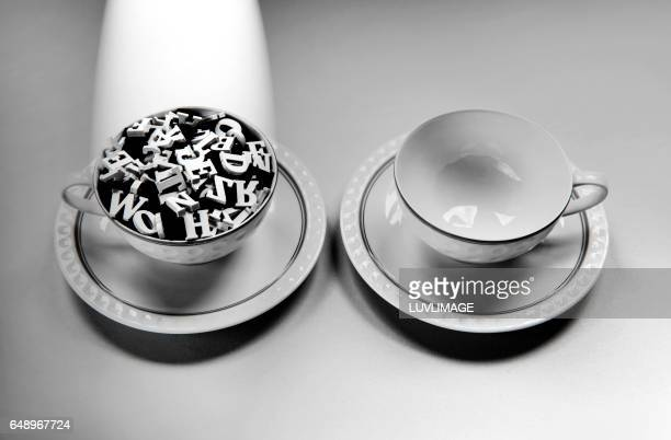 Two teacups, one filled with letters and a spotlight on it.