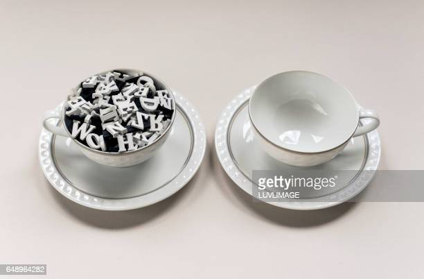 Two tea-cups with and without wooden letters in it.