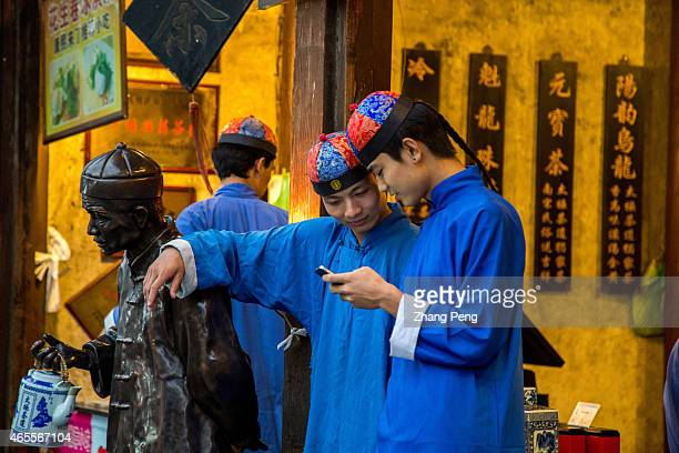 Two teashop waiters dressed in traditional costume play their smartphones while working People who have the smartphoneaddict nowadays are called...