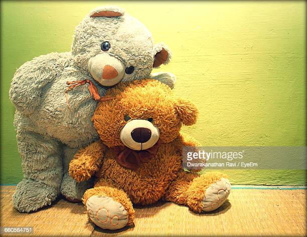 Two Teddy Bears Against Yellow Wall