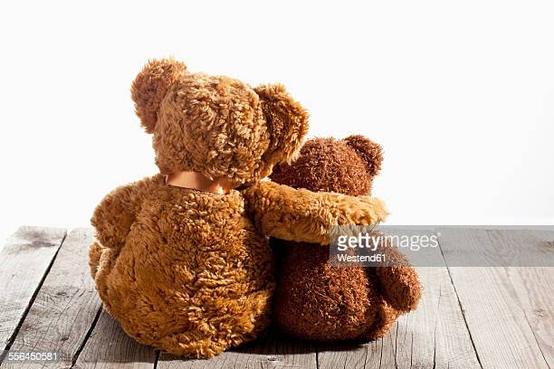Two teddy bears, arm on shoulder, back view on wood