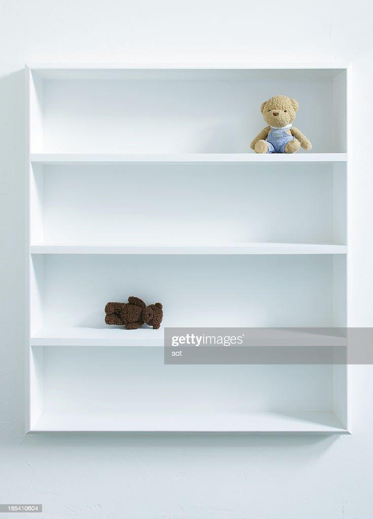 Two teddy bears in white bookshelf