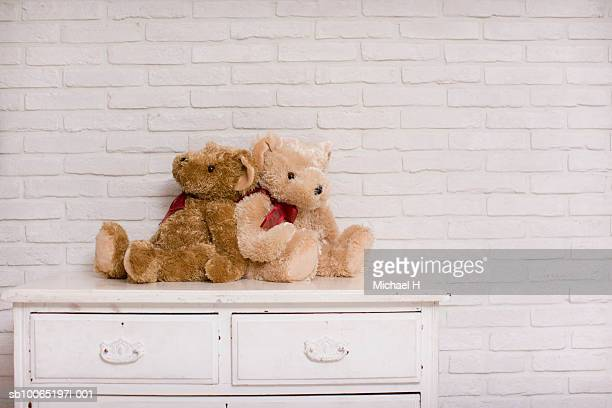 Two teddy bears sitting on chest