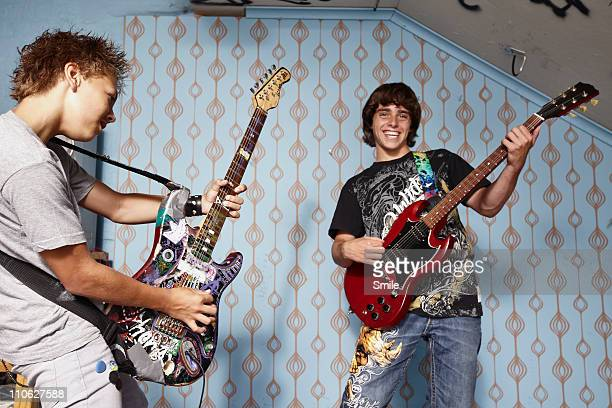 Two teen boys playing electric guitar