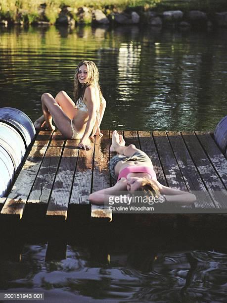 Two teen girls (13-16) relaxing on dock