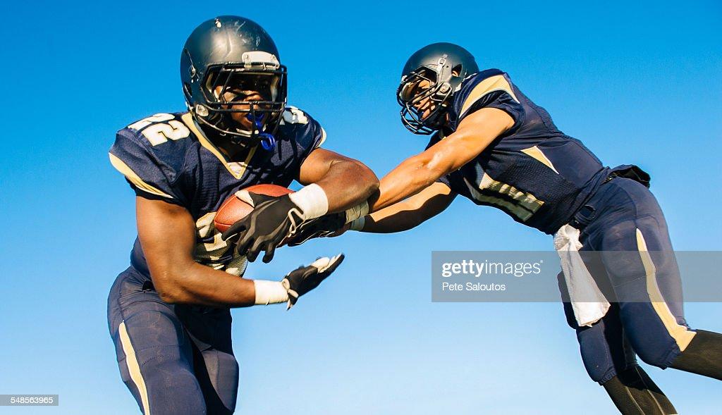 Two teenage american football players tackling ball