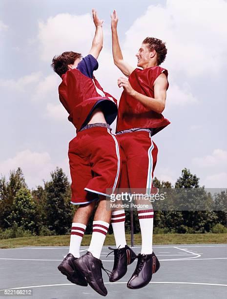 Two Teenage Basketball Players Giving High Five