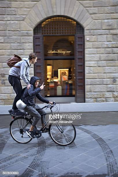 Two teenage boys have fun riding on a bicycle in Florence Italy