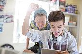 Two teenage boys having fun while using digital tablet