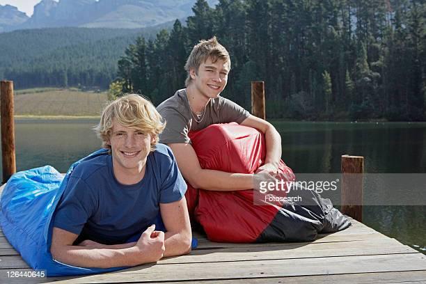 Two Teenage Boys in Sleeping Bags by Lake