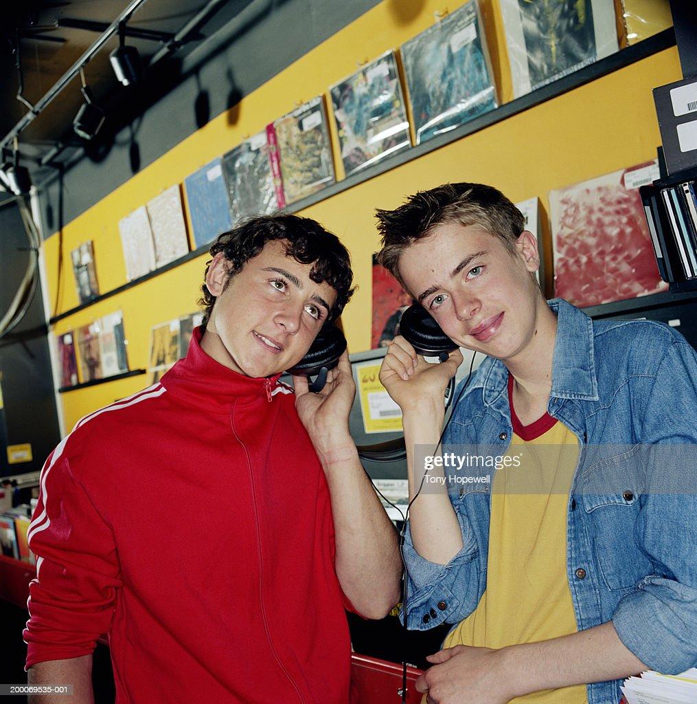 Two teenage boys  15 18  listening to headphones in record shop   Stock. Two Teenage Boys Listening To Headphones In Record Shop Stock