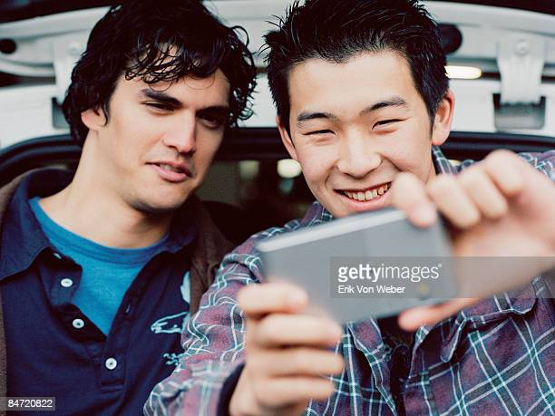 two teenage boys looking at video device