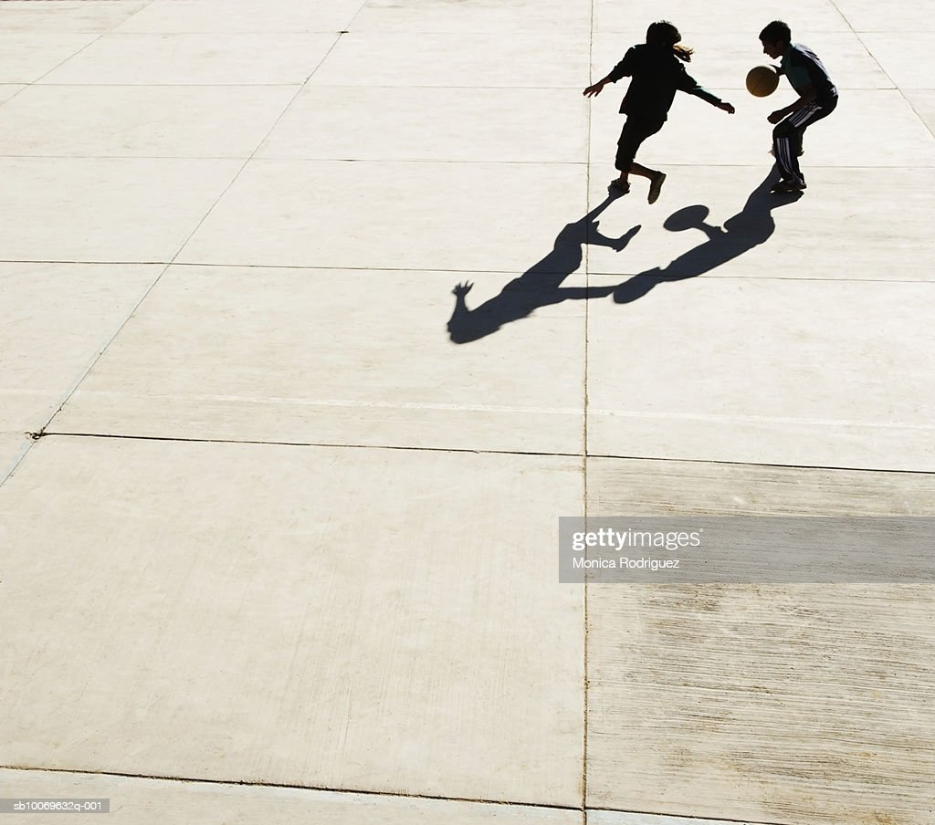 Two teenage boys (14-15) playing basketball on paving stone, elevated view : Stock Photo