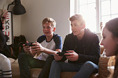 Two Teenage Boys Playing Video Game In Bedroom